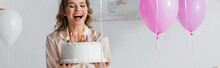 Excited Woman In Pajama Holding Birthday Cake Near Balloons, Banner