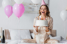 Happy Woman In Party Cap Holding Birthday Cake Near Balloons And Champagne In Bedroom