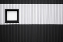 Black And White Corrugated Iron Sheet Used As A Facade Of A Warehouse Or Factory With A Window. Texture Of A Seamless Corrugated Zinc Sheet Metal Aluminum Facade. Architecture. Metal Texture.