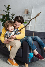 Happy Father And Child Playing Toy Fishing On Couch