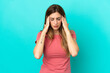 Young caucasian woman isolated on blue background with headache