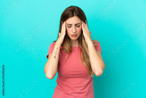 Fotografiet Young caucasian woman isolated on blue background with headache