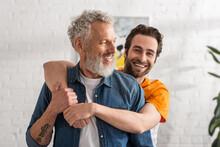 Smiling Man Hugging Mature Dad At Home