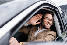 Happy Man In Glasses Looking Through Car Window And Waving Hand While Driving Auto