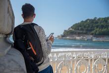 Un Hombre De Espaldas Y Con Mochila Observando La Playa De La Concha De San Sebastián Y Mirando El Móvil.