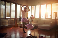 A Young Dad And His Little Daughter Practicing Ballet Moves While They Have A Training At Home Together. Family, Together, Home