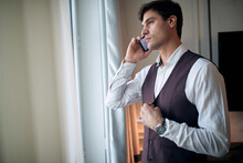 Pensive Young Caucasian Male Talking On A Cell Phone By The Window, Fastening Buttons On His Vest With Another Hand