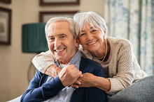 Happy Senior Couple Embracing At Home With Love
