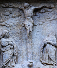 Biblical History: Crucifixion Of Jesus Christ, Virgin Mary And Mary Magdalene. Ancient Stone Statue.