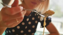 Beautiful Blonde With Glasses Eats Spaghetti Carbonara In A Restaurant.