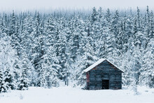 Old Wooden Barn In Front Of Snow Covered Forest