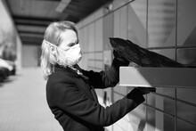 Lady Wearing A Face Mask Receives A Parcel Or Package From A Post Parcel Terminal In Tallinn. Woman Wearing A Face Respiratory Mask -protecting From Viruses, Contaminated Environment.