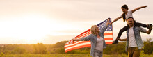 Family Holding Up An American Flag In A Field.