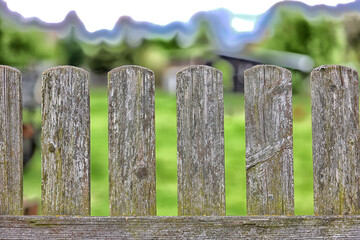 Stary drewniany płot ze sztachet na wsi.
