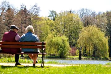 Zdjęcie przedstawiające parę starszych ludzi siedzącą na ławce w parku