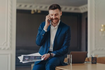 Happy handsome businessman talking on phone while sitting on table at luxury apartment
