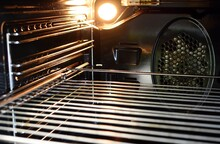 A View Of The Inside Of An Empty Oven With Lighting Bulb And A Wire Rack.
