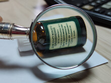 The Inscription On The Bottle And The Magnifying Glass. Enlargement Of Letters. Small Print, Green Tone. Shallow Depth Of Field, Poor Vision After 40.