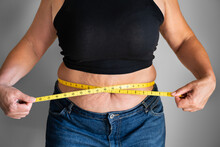 Caucasian Woman With Belly Fat Using Tape Measure