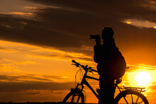 Silhouette Of Male Photographer Cyclist Stands On The Road And Looks Into The Distance And Admires The Beautiful Landscape At Crimson Sunset.