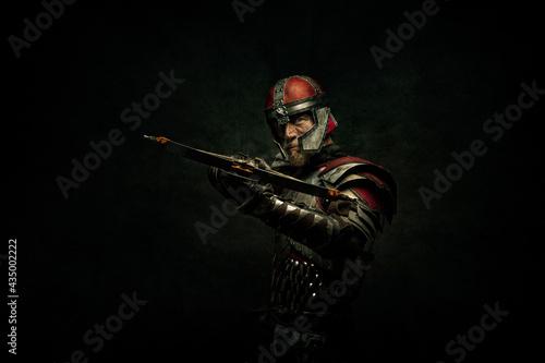 Billede på lærred Portrait of a medieval fighter holding a crossbow in his hands