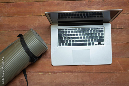 Foto top view of laptop and gray yoga mat in studio. sports concept