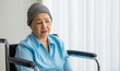 Older Asian woman patient covered the head with clothes effect from chemo treatment in cancer cure process lonely sitting on wheelchair and wait for someone to visit her