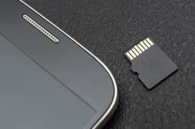 Micro SD Memory Card With Smartphone. Close Up.