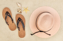 Flip Flops With Beach Hat And Seashells On Sand. Top View. Vacation Concept.