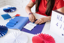 Beautiful Woman Making DIY Paper Fans Of Red And Blue Colors, Celebrating Independence Day Of The USA. Happy 4 July The Text On The Lightbox