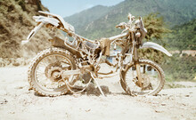 Abandoned Old Motocross Motorcycle Be Drowned In Deep Road Dust Near The Crowed Town Road In Ramechhap, Nepal.