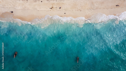 Fotografiet Aerial shot of the white sand beach shore and emerald water with fishermen's boats floating on Indian ocean waves on the Zanzibar island, Tanzania