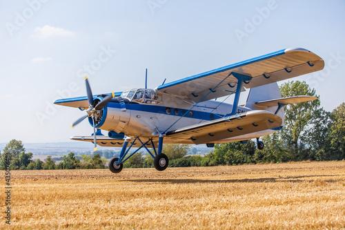 Wallpaper Mural Antonov AN-2 Flugzeug Doppeldecker beim landen Landeanflug auf dem Acker