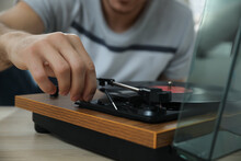 Man Using Turntable At Wooden Table Indoors, Closeup