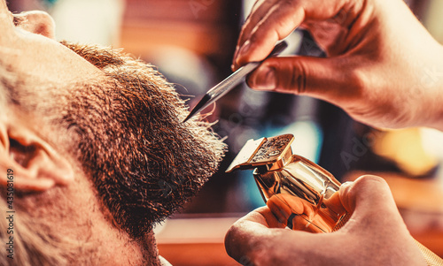 Bearded man in barbershop. Man visiting hairstylist in barbershop. Barber works with a beard clipper. Hipster client getting haircut. Hands of a hairdresser with a beard clipper, closeup
