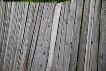 A Rickety Gray Unpainted Old Fence With Sloping Boards