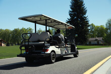 People In Golf Cart On Road Outdoors