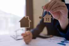 Real Estate Agent Sales Manager Holding Keys To Customer And Holding Sign House Offer For And House Insurance.home Owner, Rental Property Purchase, Mortgage Investment Loan, Ownership Concept.