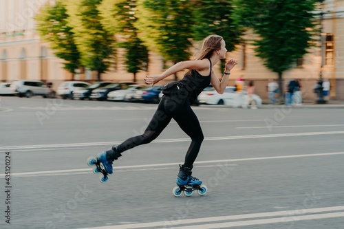 Fotografia Professional female roller demonstrates her abilities of rollerblading rides very quckly on road along city enjoys sunny day dressed in black active wear