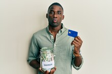 Young African American Man Holding Credit Card And Jar With Dollars Puffing Cheeks With Funny Face. Mouth Inflated With Air, Catching Air.