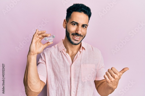 Fotografiet Young hispanic man holding brilliant diamond stone pointing thumb up to the side