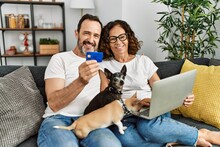 Middle Age Hispanic Couple Using Laptop And Credit Card. Sitting On The Sofa With Dogs At Home.