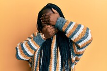 Young Black Woman With Braids Wearing Casual Winter Sweater Covering Eyes And Mouth With Hands, Surprised And Shocked. Hiding Emotion