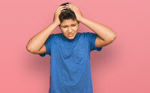 Teenager Hispanic Boy Wearing Casual Clothes Suffering From Headache Desperate And Stressed Because Pain And Migraine. Hands On Head.