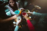 Happy friends drinking together at cocktail bar restaurant - Group of young people enjoying night out toasting drinks on happy hour - Top view