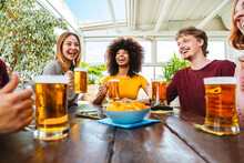 Happy Multiracial Friends Group Drinking Beer At Brewery Pub Restaurant - Friendship Concept With Young People Having Fun Drinks On Happy Hour - Focus On Black Woman
