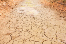 Drought Cracked Ground Earth On Top View. Crack Soil Surface Texture. Background On Hot Arid Climate Weather. Brown Broken Ground. Global Warming And Environmental Crisis.