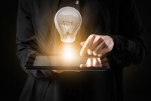 Businesswoman With Tablet Computer And Glowing Light Bulb On Dark Background, Closeup