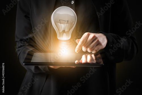 Obraz na plátně Businesswoman with tablet computer and glowing light bulb on dark background, cl