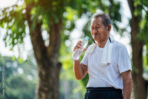Happy thirsty senior man drinking fresh water after sports in park, Concept of senior healthy lifestyle Fototapet